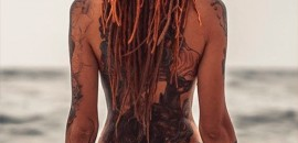 Naked girl in tattoos and long dreadlocks